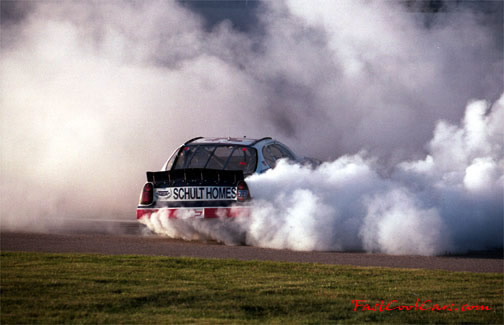 Racecar smoldering the tires in a few victory donuts