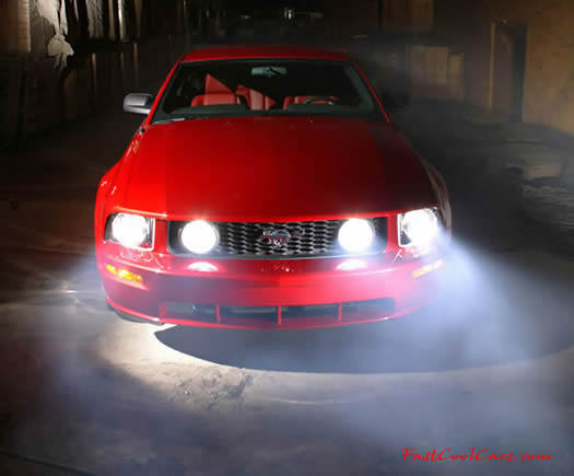 2005 Ford Mustang GT front view at night with headlights on